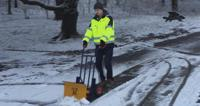 Man in high vis jacket clearing snow
