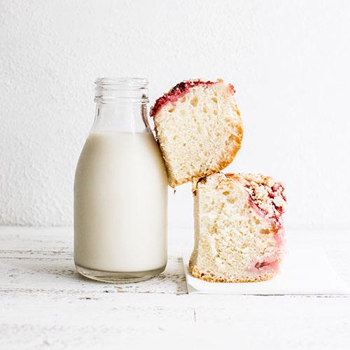 2 square pieces of cake are balanced against a small glass bottle of milk.