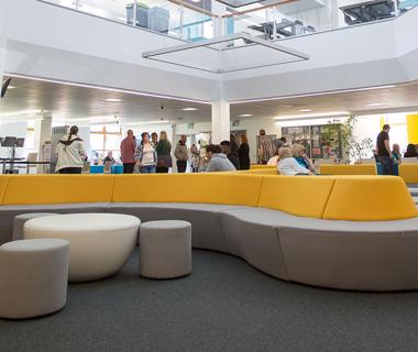 Groups of students walking around and sitting on modern yellow and grey sofas in a large, open study space.