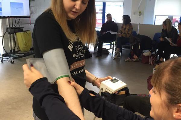 A female trainee occupational therapist is applying a blood pressure monitor to a female student's arm as a practical on our occupational therapy degree.