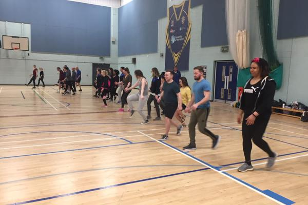 A group of student occupational therapists doing a walking exercise in the sports hall on our occupational therapy degree.