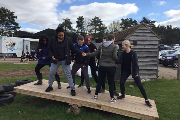 A group of student occupational therapists balancing on a wooden seesaw for a team building activity on our occupational therapy degree.