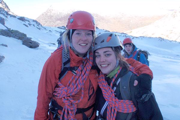 Two women with climbing gear standing on a snowy mountain