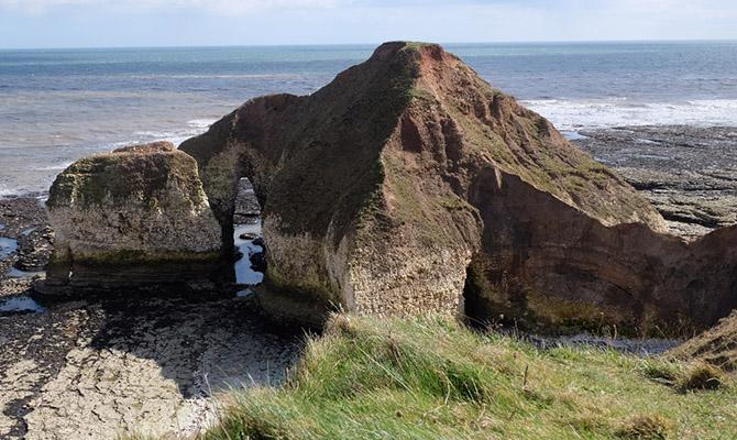 View of rocky outcrop with sea behind