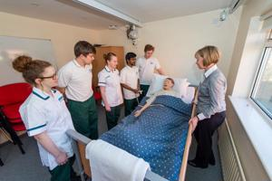 Five student nurses and a lecturer at the bedside of a synthetic patient