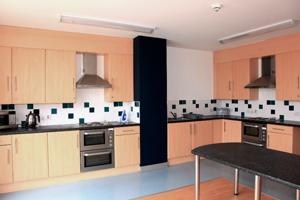 inside a communal kitchen with wall cupboards and fitted ovens