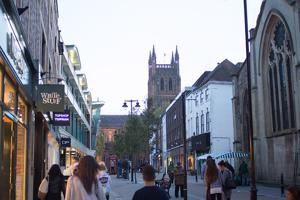 a couple holding hands in the street with worcester cathedral in the distance