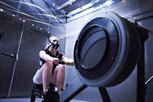 girl wearing a mask on a rowing machine