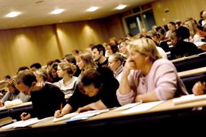 inside a lecture theatre with multiple students at their desks