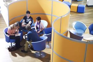 elevated view of students on blue seats in front of a yellow partition