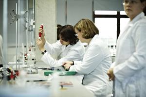 three students in a laboratory setting wearing white protective clothing