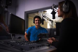 two people either side of a radio desk speaking into microphones
