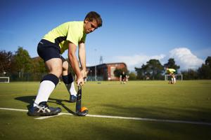 man in a yellow top about to strike a hockey ball onto the pitch