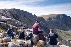 students studying on rocks on a mountain