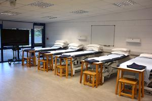 a row of beds within a lecture room set out as a ward