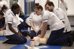 several student nurses kneeling beside a clinical dummy
