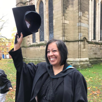 Woman in graduation robes holding a hat above her head
