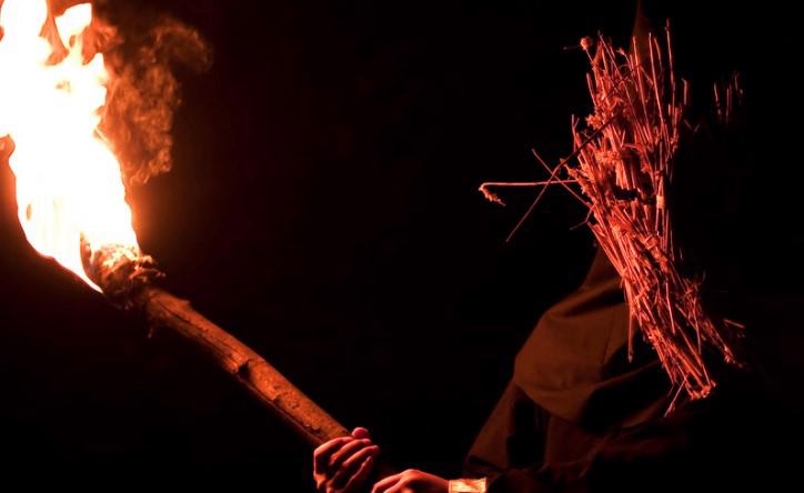 A man with sticks covering his face is holding a flaming torch