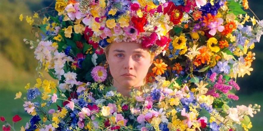 A girl is covered in many brightly coloured flowers