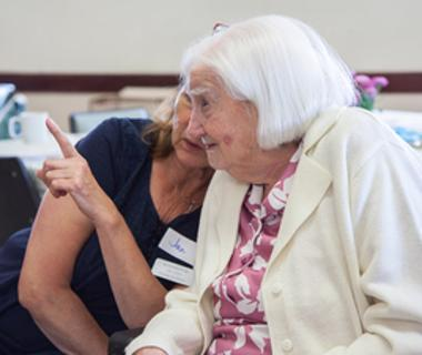 An elderly lady with white hair converses with a friend