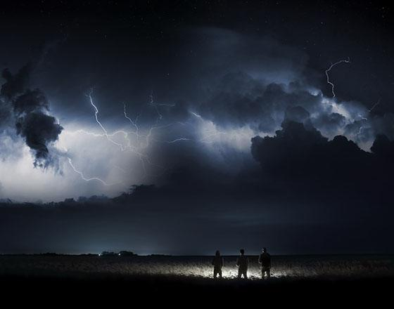 Three people stand silhouetted in a field at night as lightening strikes the sky