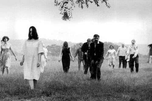 A group of zombies walk towards the camera through a field in this film still