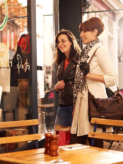 A picture of two women entering a cafe. In front of them is a table containing a salt and pepper mill.