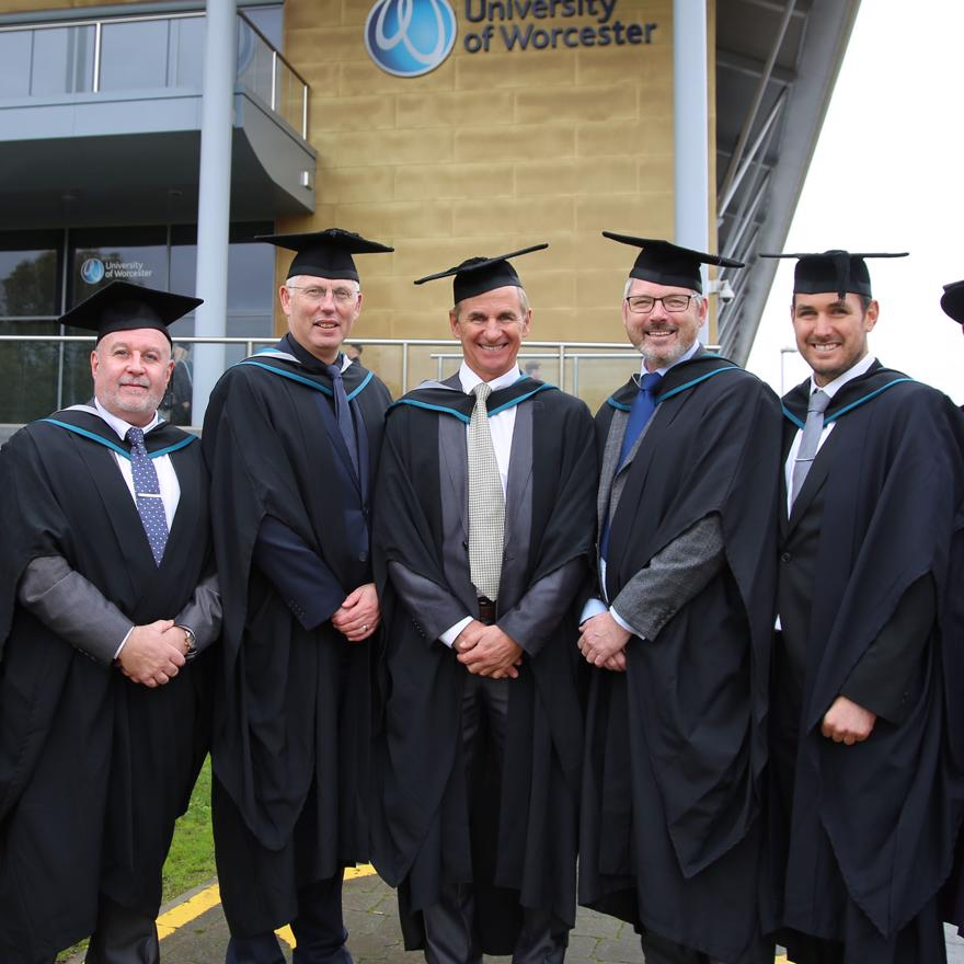 A group of men wearing graduation robes and mortarboards
