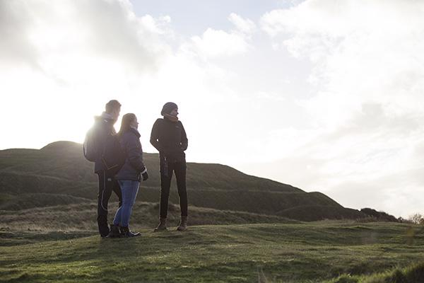 Three students are silhouetted by the sun at the top of the Malvern Hills