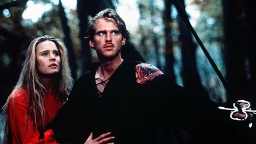 A man in black defends a woman in red with a sword in a forest