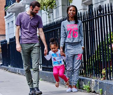 A family are walking down the street with their child