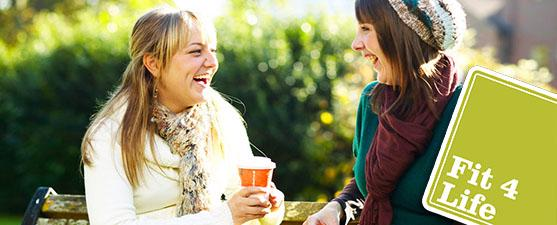 Students laugh outdoors while drinking coffee