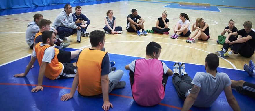 Sports students sit in a circle in a sports hall