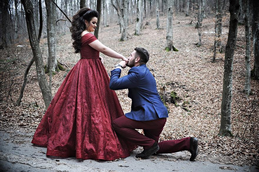 Man kissing the hand of a woman in a red dress while in the woods