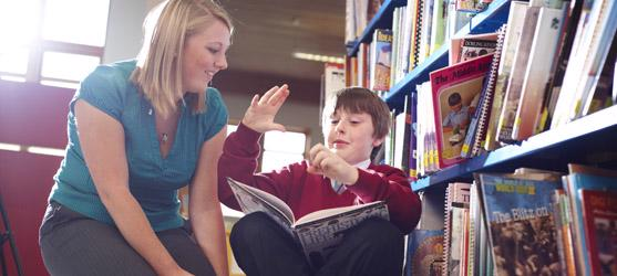 A teaching student teaching a student in a library