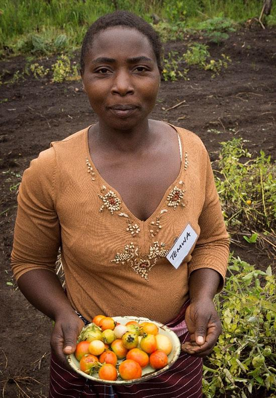 A lady called Temwa is standing in a welt land area holding a tray of fruit