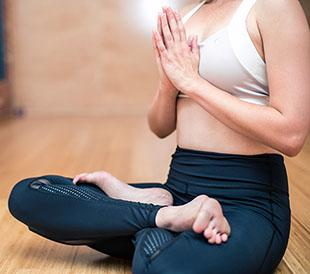 A woman is sitting crosslegged in a yoga position