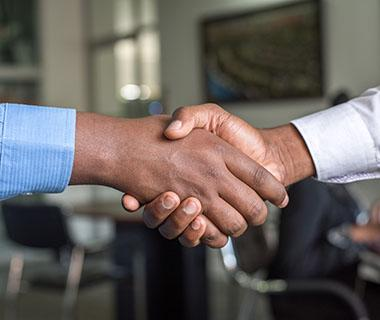 A close up shot of two people shaking hands