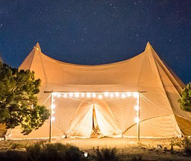 Beige tent at night with twinkling lights on the foreground