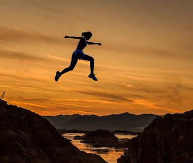 A woman is jumping high in the air during the sunset