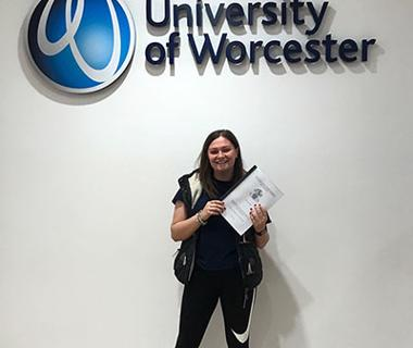 Young woman underneath the university of worcester sign and logo
