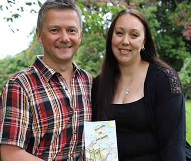 Man in checked shirt and woman in black top holding a book