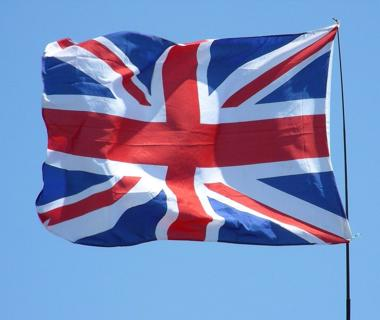 A union Jack flag is flying against a blue sky
