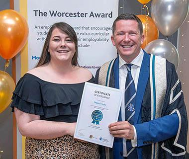 A student is receiving her Worcester Award Certificate from Ross Renton