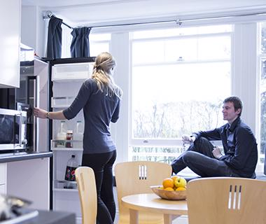 A male and female student in a kitchen in University halls of residence