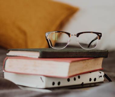 A pair of glasses are placed on top of several books