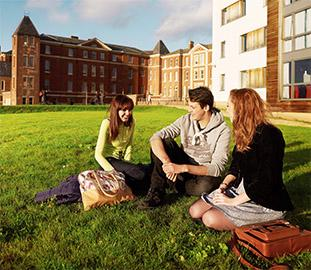 Three students sitting on the grass in front of city campus