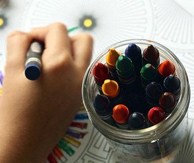 A close up shot of a child's hand colouring in a page next to a pot of colouring pencils.