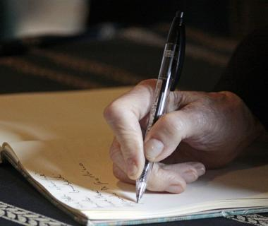 A hand is writing in a book