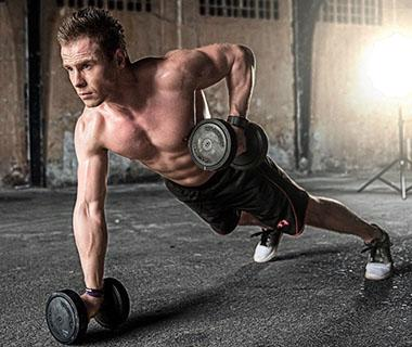 A man us lifting weights whilst doing a press up